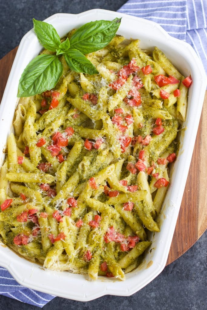 A white casserole dish filled with pesto pasta and fresh basil on a dark background next to a blue striped napkin.