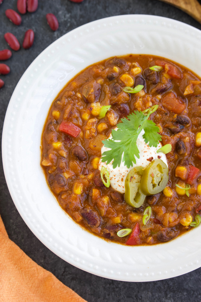Chili with toppings in a white bowl on a dark background.