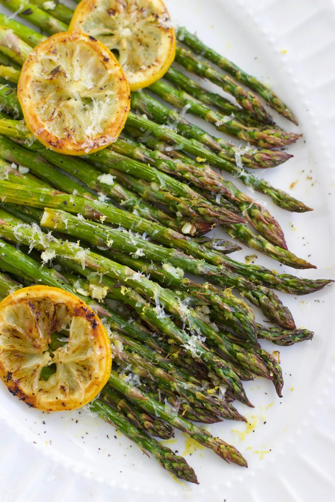 A large white platter filled with roasted asparagus topped with lemon slices and parmesan cheese.