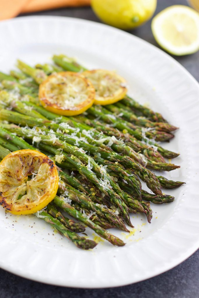 Roasted asparagus with garlic and lemon slices on a large white platter.