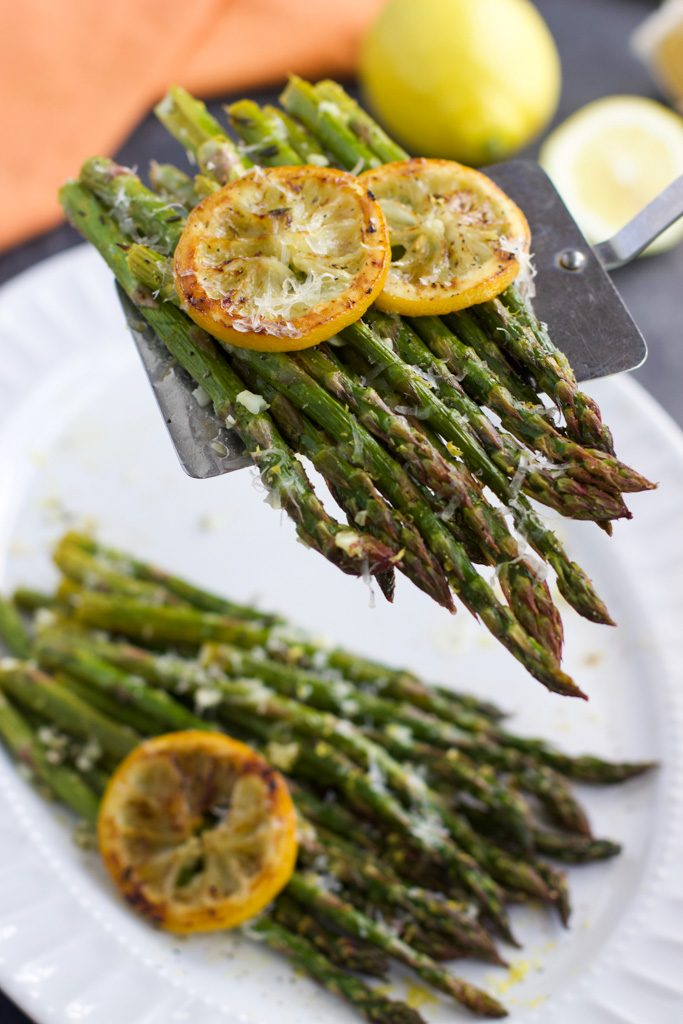 A metal spatula holding roasted asparagus over a large white platter.