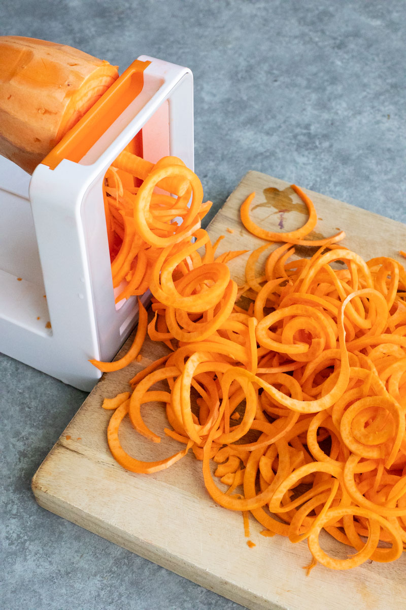 A sweet potato being spiralized into noodles onto a wooden cutting board on a gray background.