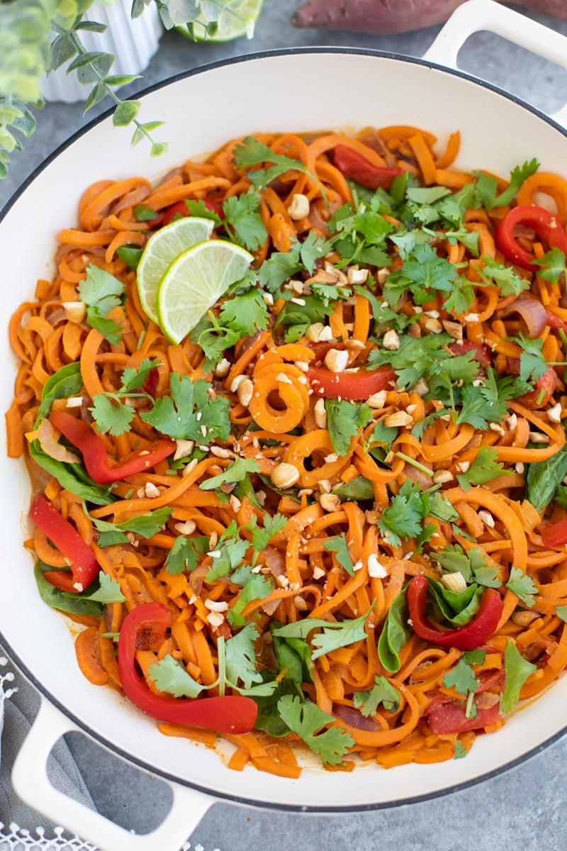 A white pan filled with vegan peanut noodles with lots on toppings on a gray background.