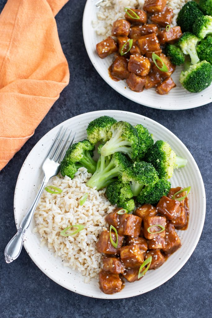 Two plates with crispy baked tofu, roasted broccoli, and brown rice on a dark background.