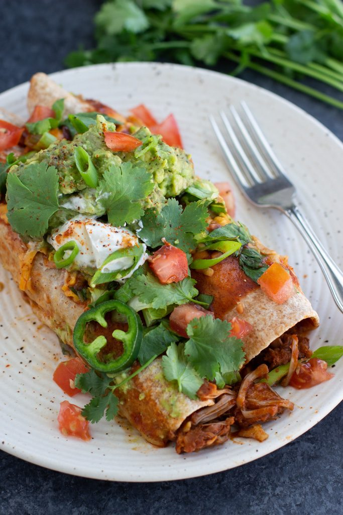 Two vegan enchiladas topped with sliced jalapeños, guacamole, tomatoes, and cilantro on a white textured plate with a fork.