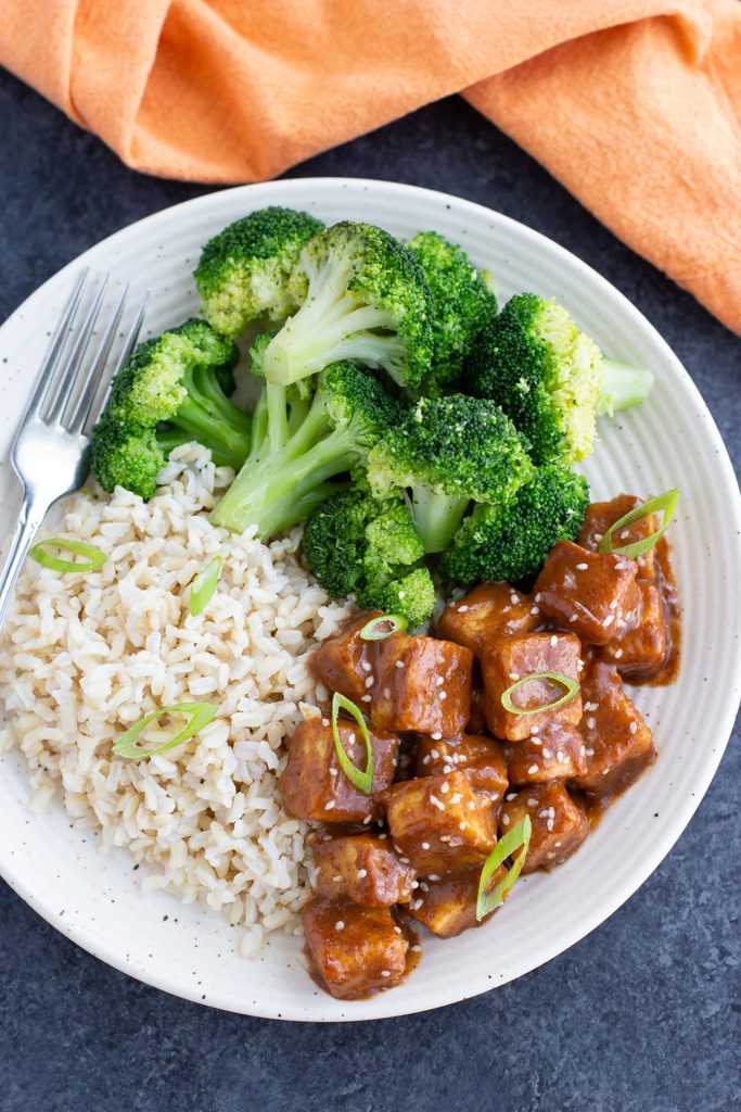 Crispy baked tofu with brown rice and broccoli on a white plate with an orange napkin on a dark background.