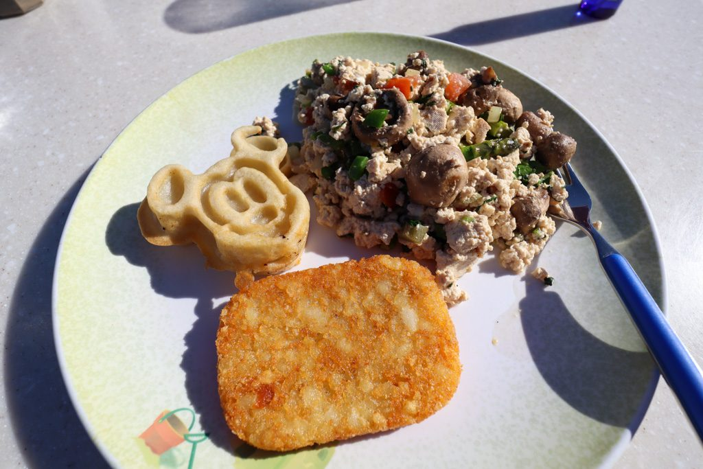 A plate with a Mickey waffle, tofu scramble, hash brown, and a fork on a table.