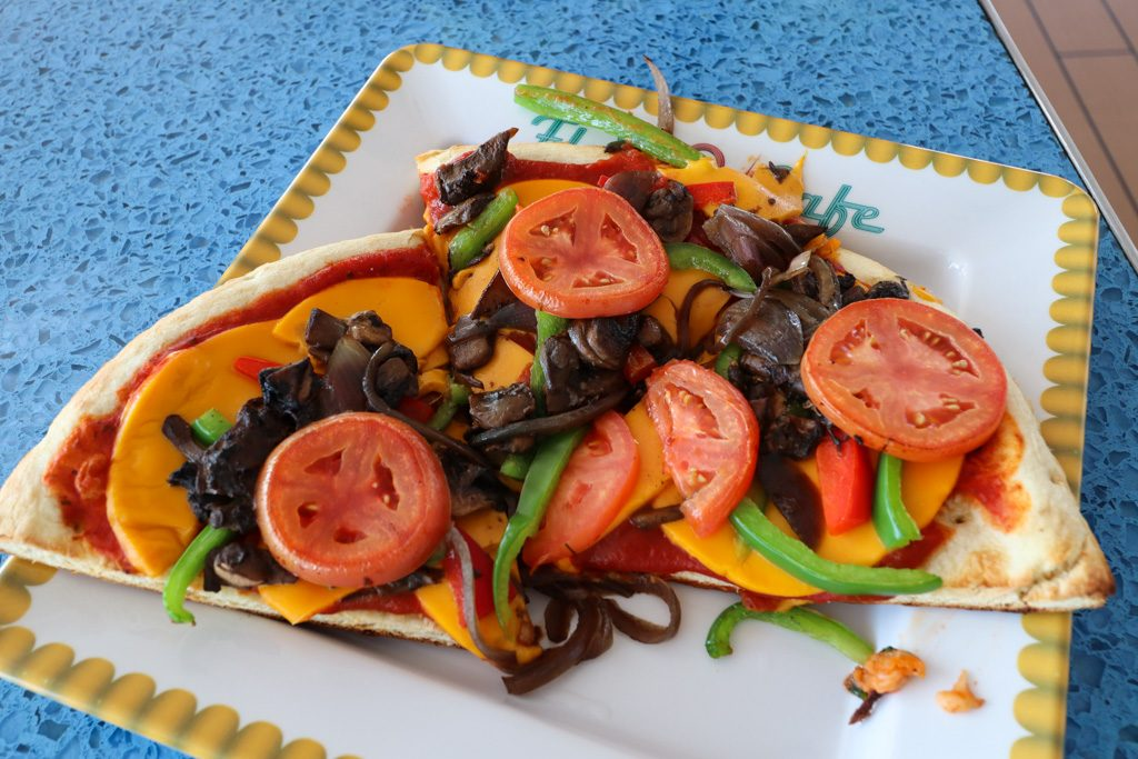 Vegan vegetable pizza on a yellow-trimmed plate sitting on a textured blue table.