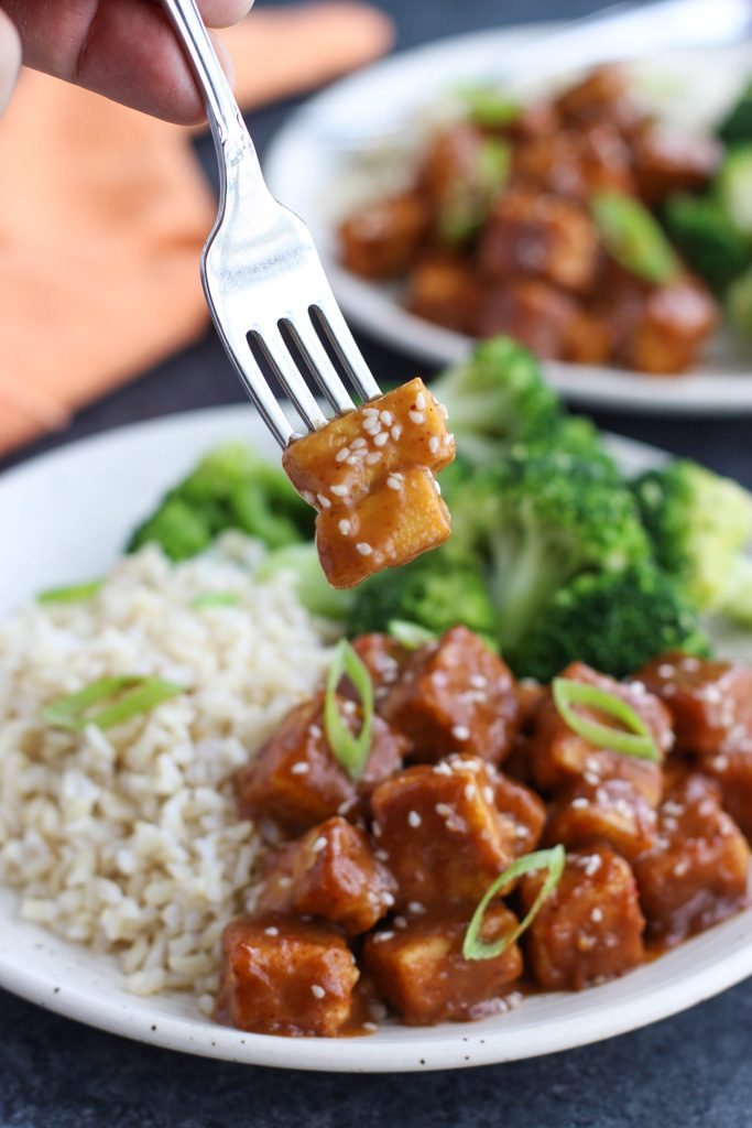 A hand holding a fork that's spearing two pieces of crispy baked tofu over a plate of broccoli and rice.