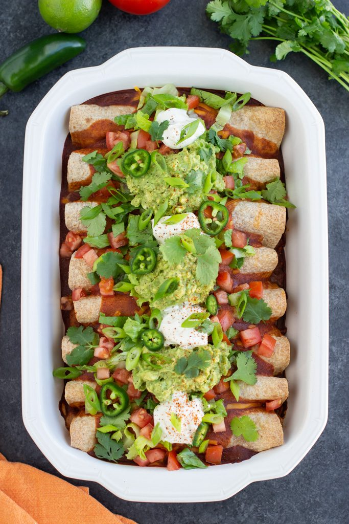A large white casserole dish filled with vegan enchiladas and lots of toppings on a dark textured background.