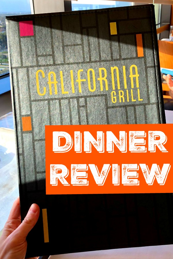 A hand holding the California Grill menu up at a table.