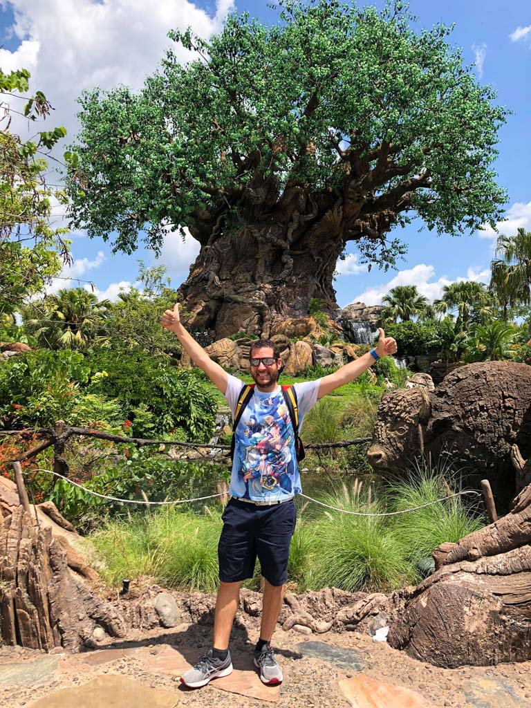 A young man with his hands above his head is standing in front of the Tree of Life at the Animal Kingdom.