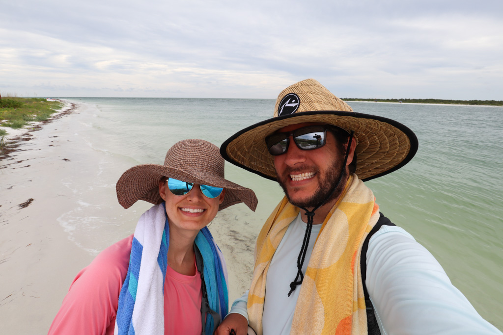 A smiling couple posing on the beach at Caladesi Island State Park.