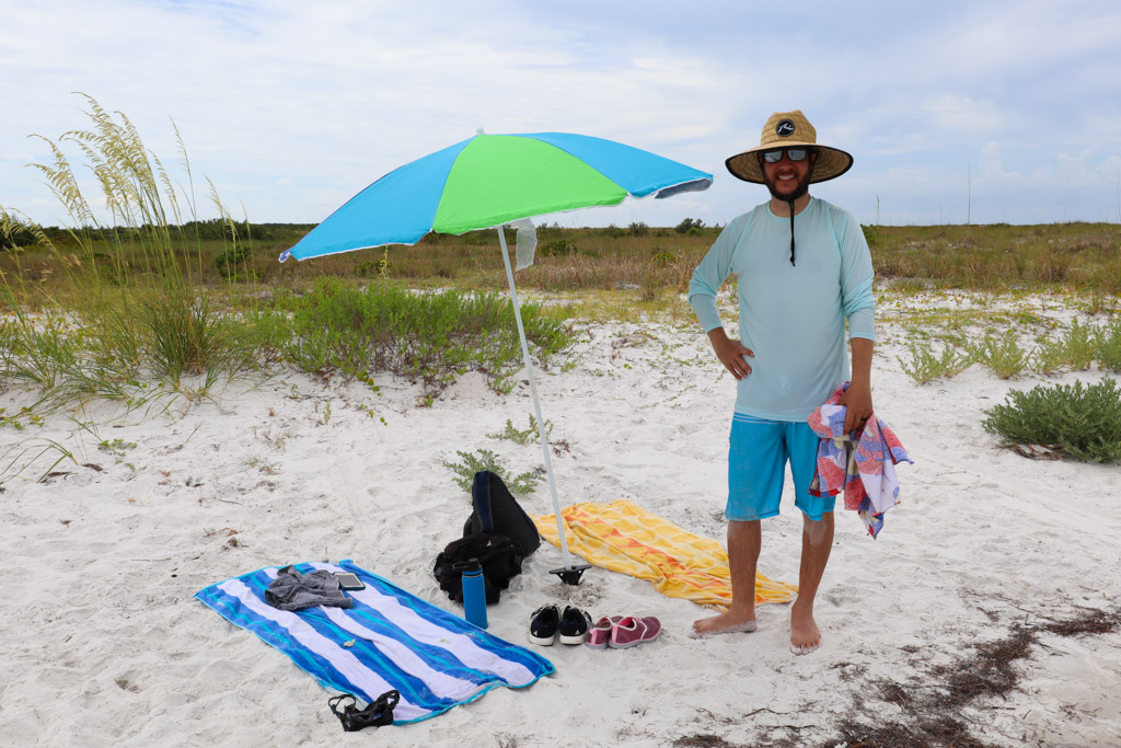 A man standing next to a beach umbrella with towels laid on the ground at Caladesi Island.