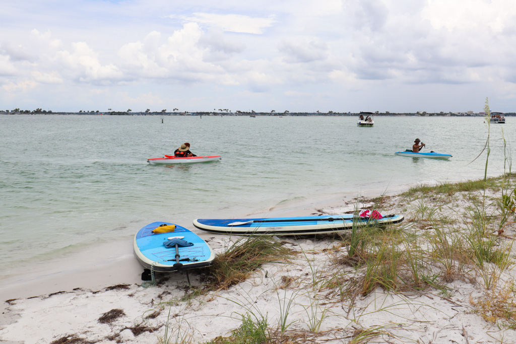 People kayaking to the shore on Caladesi Island beach.