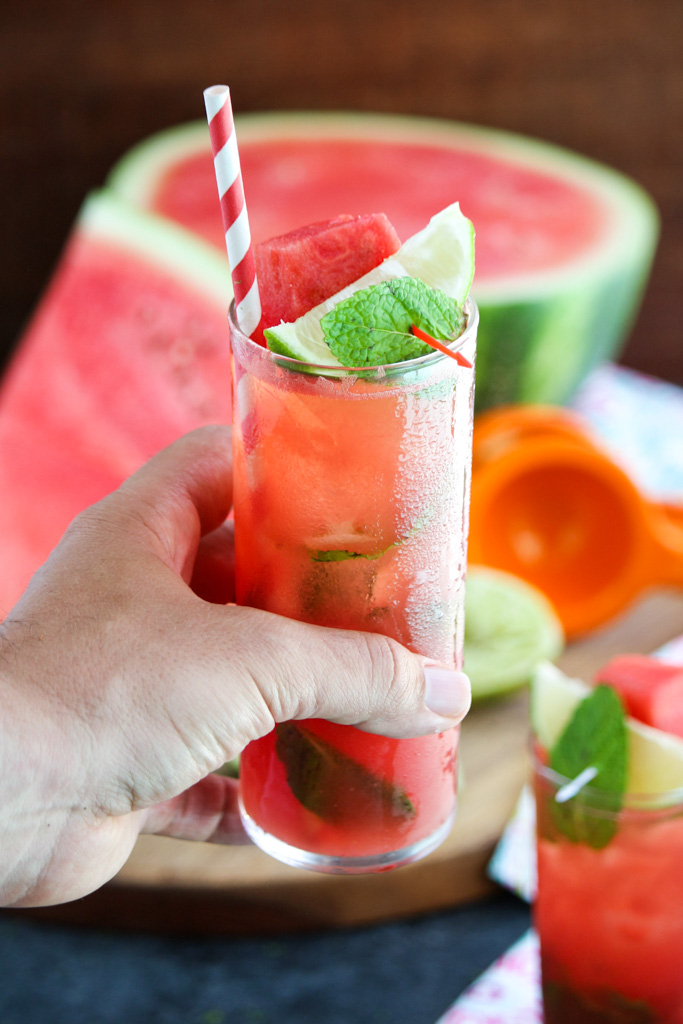 A hand holding a watermelon Moscow mule in a tall glass with a red striped straw.