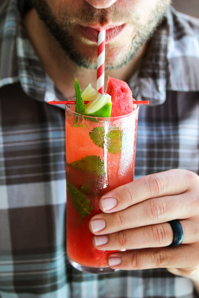 A man drinking a watermelon Moscow mule through a paper straw out of a glass.