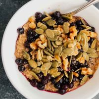Vegan cinnamon oatmeal topped with nuts, seeds, and frozen blueberries in a white bowl.