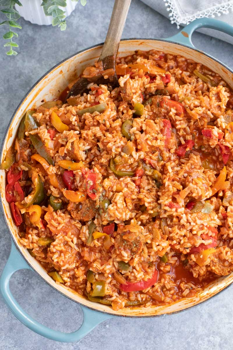 A large blue pan filled with vegan sausage, peppers, and rice on a gray background.