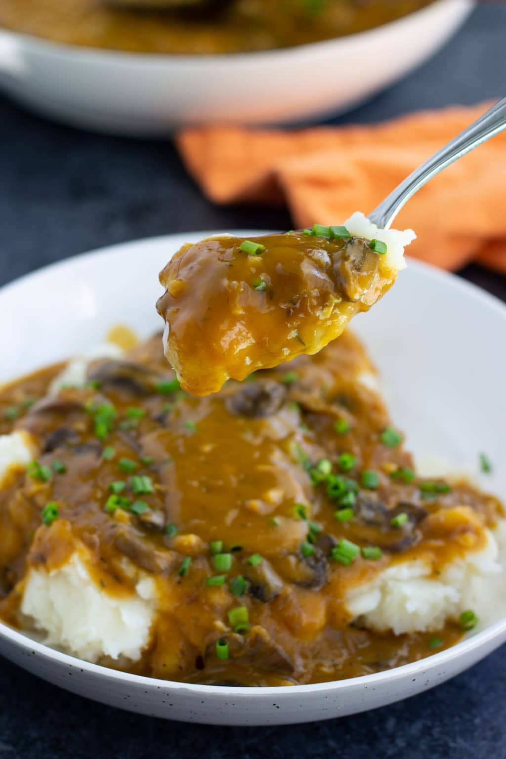A spoonful of mashed potatoes topped with vegan gravy and chives over a white bowl next to an orange napkin on a dark background.