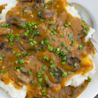 A white bowl filled with mashed potatoes, mushroom gravy, and chives.