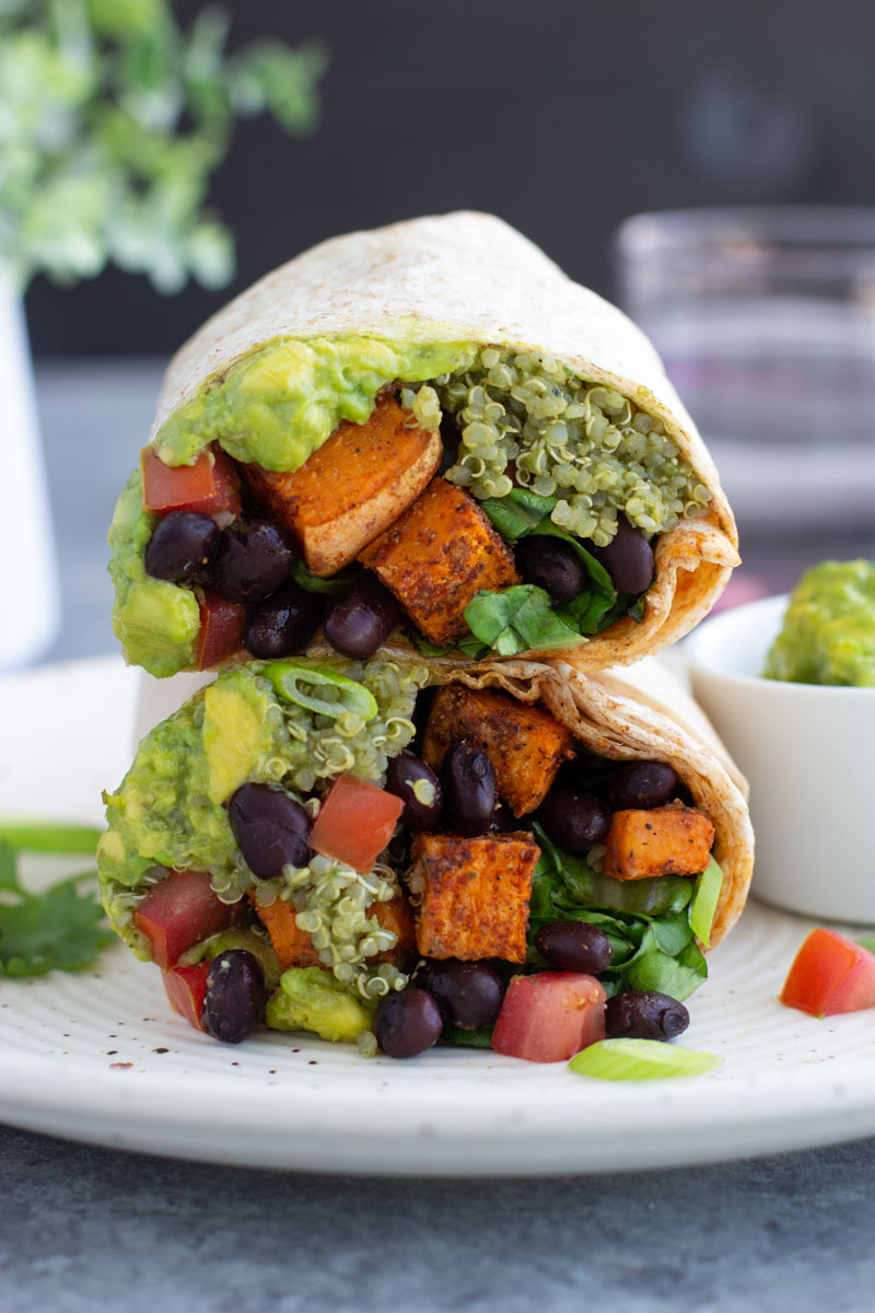 A close up view of two halves of a vegan burrito stacked on top of each other.