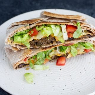 A vegan crunchwrap supreme on a white plate.