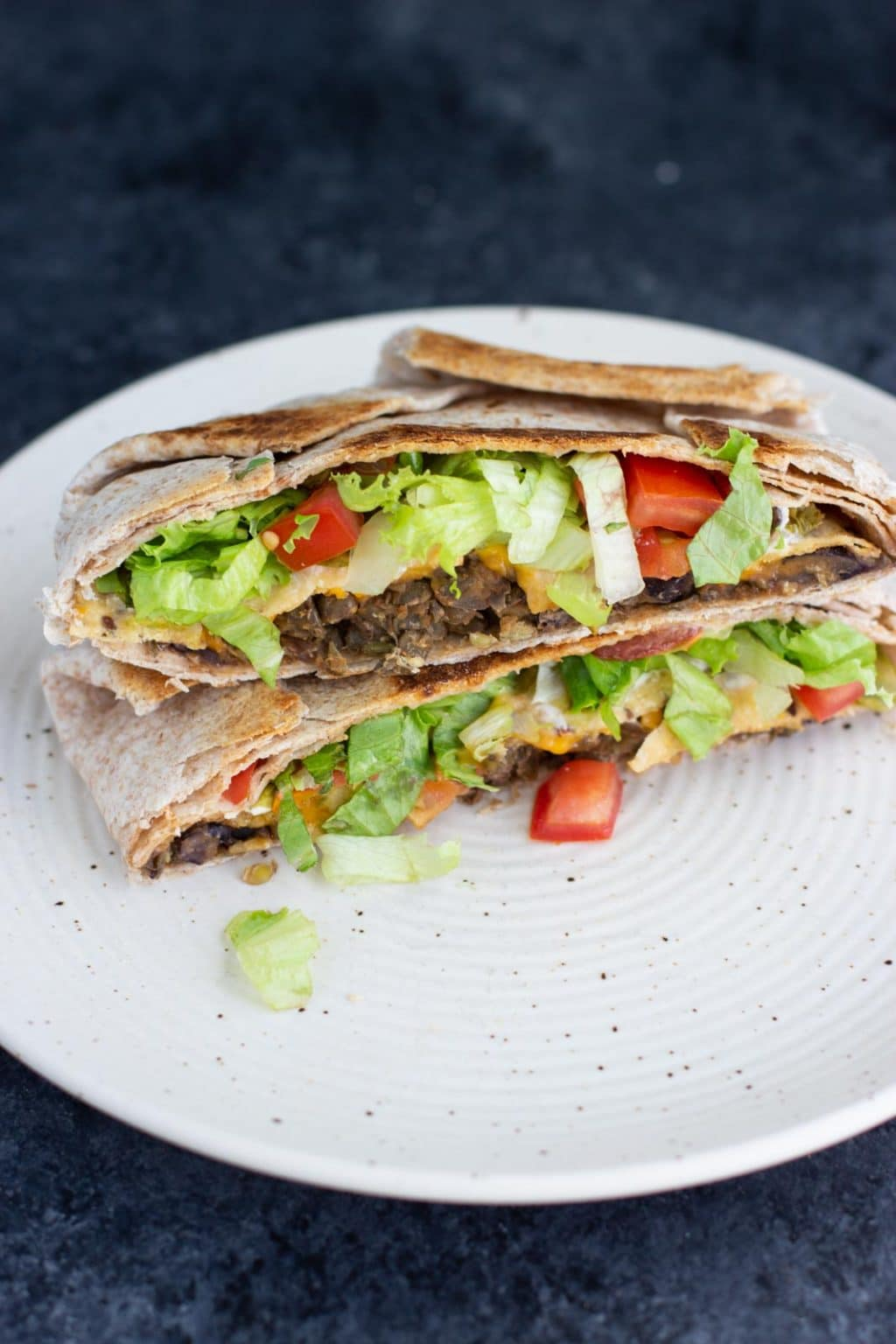 A vegan crunchwrap supreme cut in half and stacked on top of each other on a white plate on a dark background.