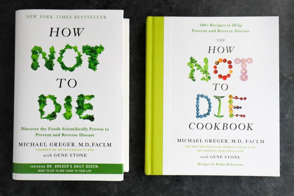 How Not to Die and the How Not to Die Cookbook next to each other on a dark background.