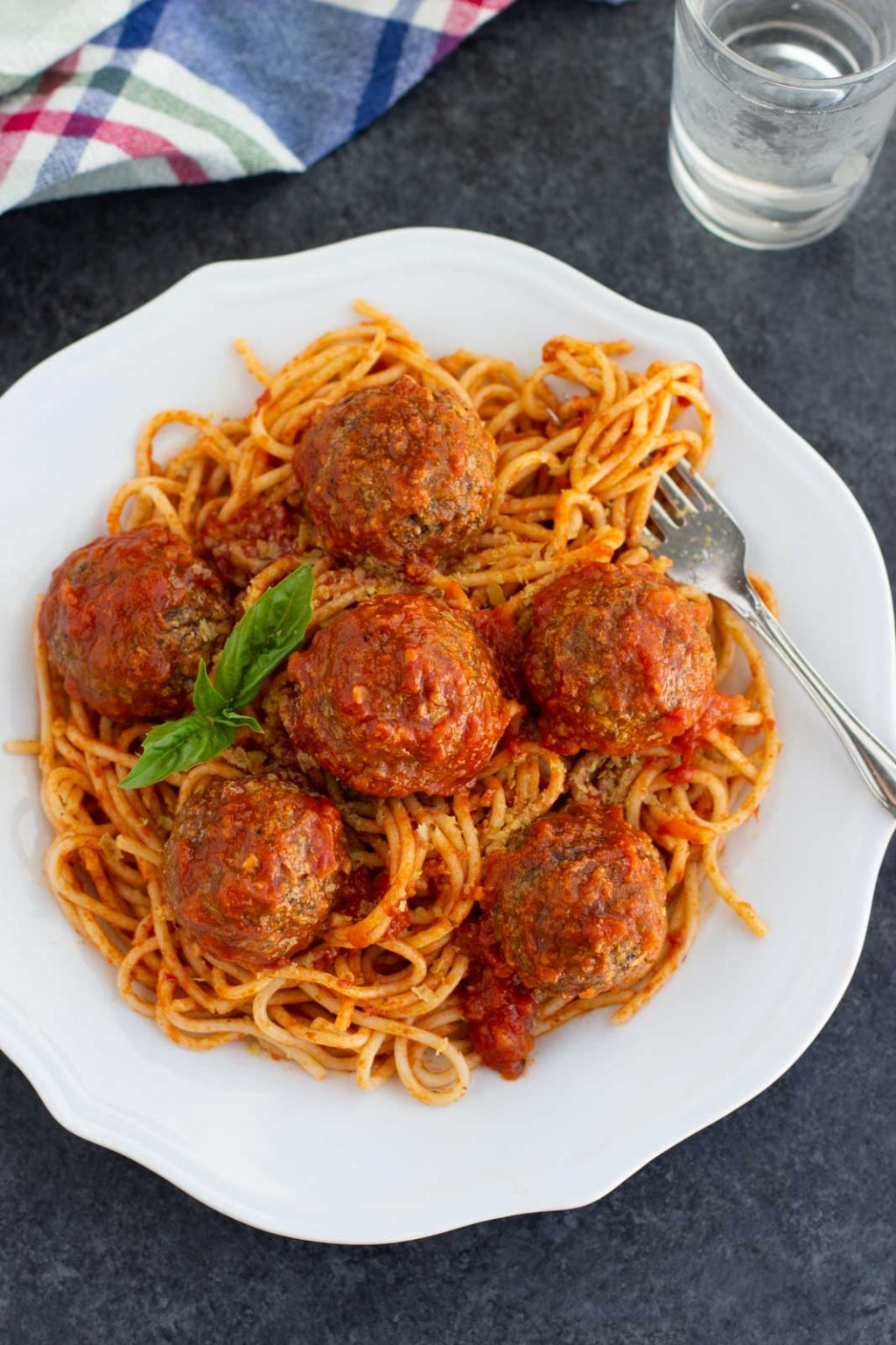 A white plate filled with vegan meatballs and spaghetti on a dark background.