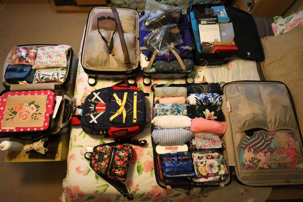 Multiple suitcases opened on a bed so you can see all of the clothes and items that are packed inside.