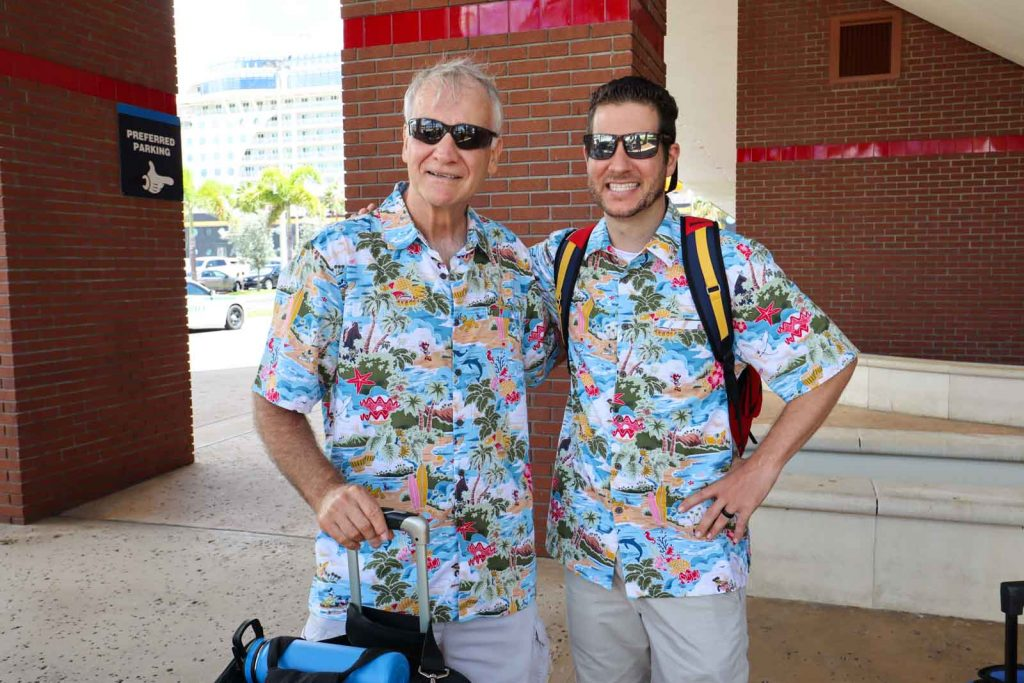An older and younger man smiling and dressed in matching Disney cruise shirts.
