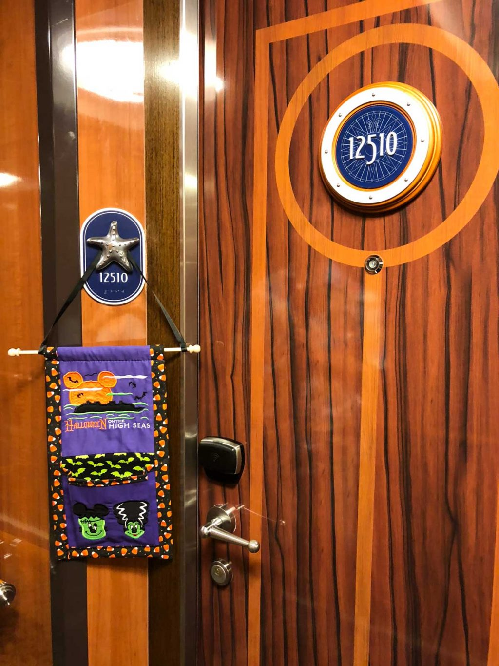 A purple fish extender hanging on a concierge stateroom door #12510 on the Disney Fantasy.
