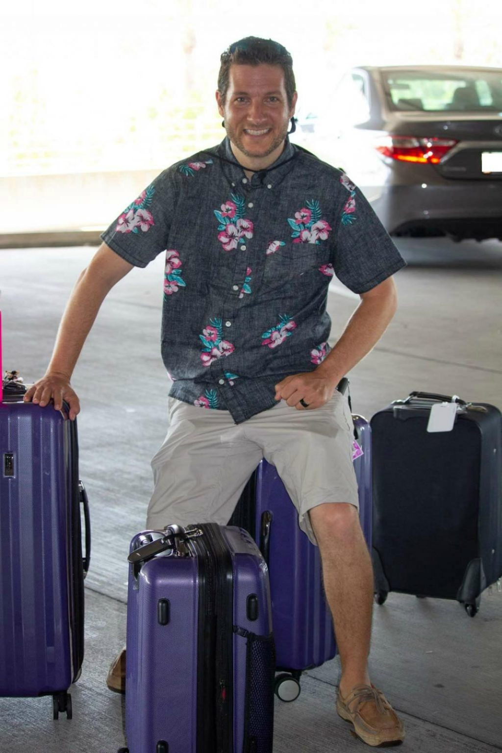 A man in a floral shirt is sitting on top of a purple suitcase with a few suitcases next to him.