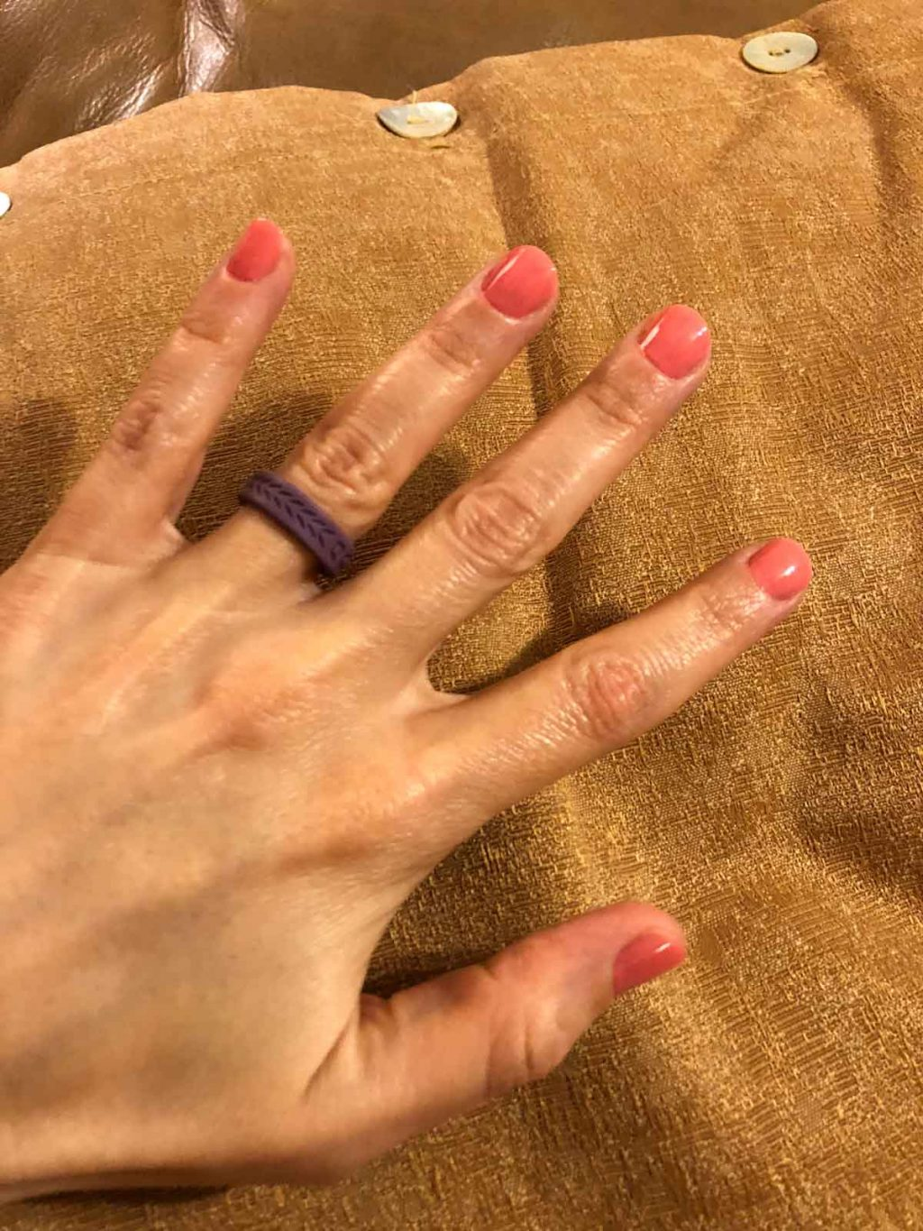 A woman's hand with painted pink nails and a purple qalo ring.