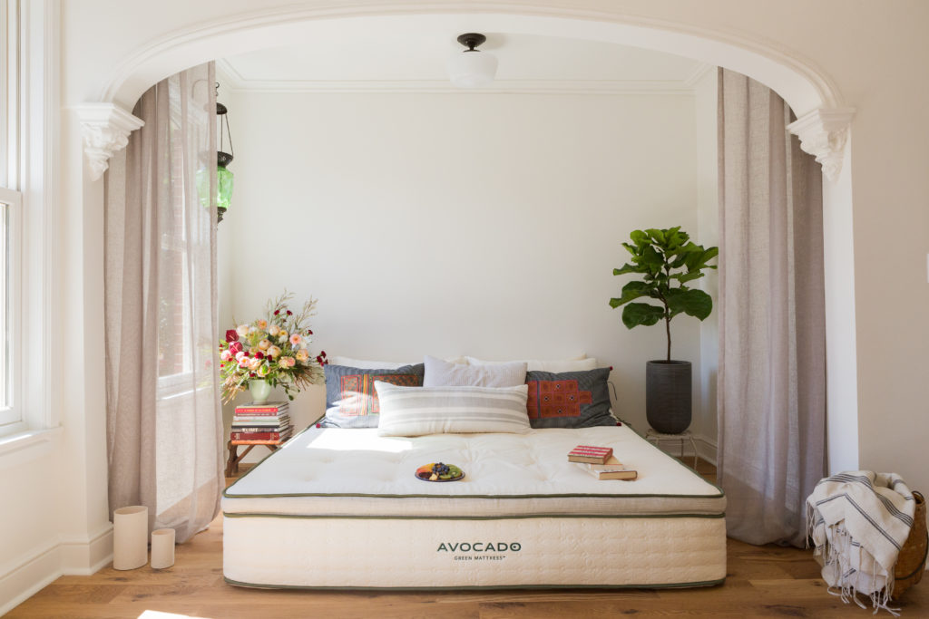 An Avocado green mattress on the floor in a light and airy bedroom.
