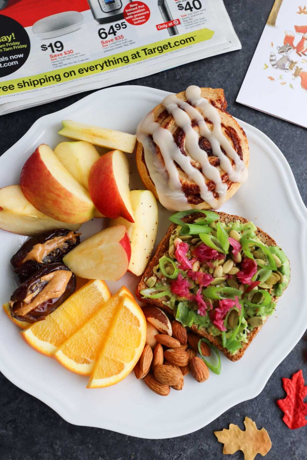 A white plate filled with avocado toast, cinnamon rolls, apple slices, orange slices, and dates.
