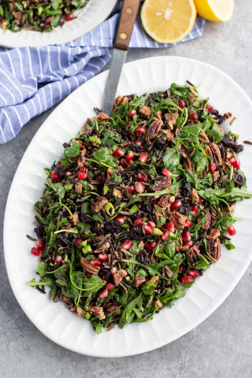 A white platter filled with arugula wild rice Christmas salad on a gray background.