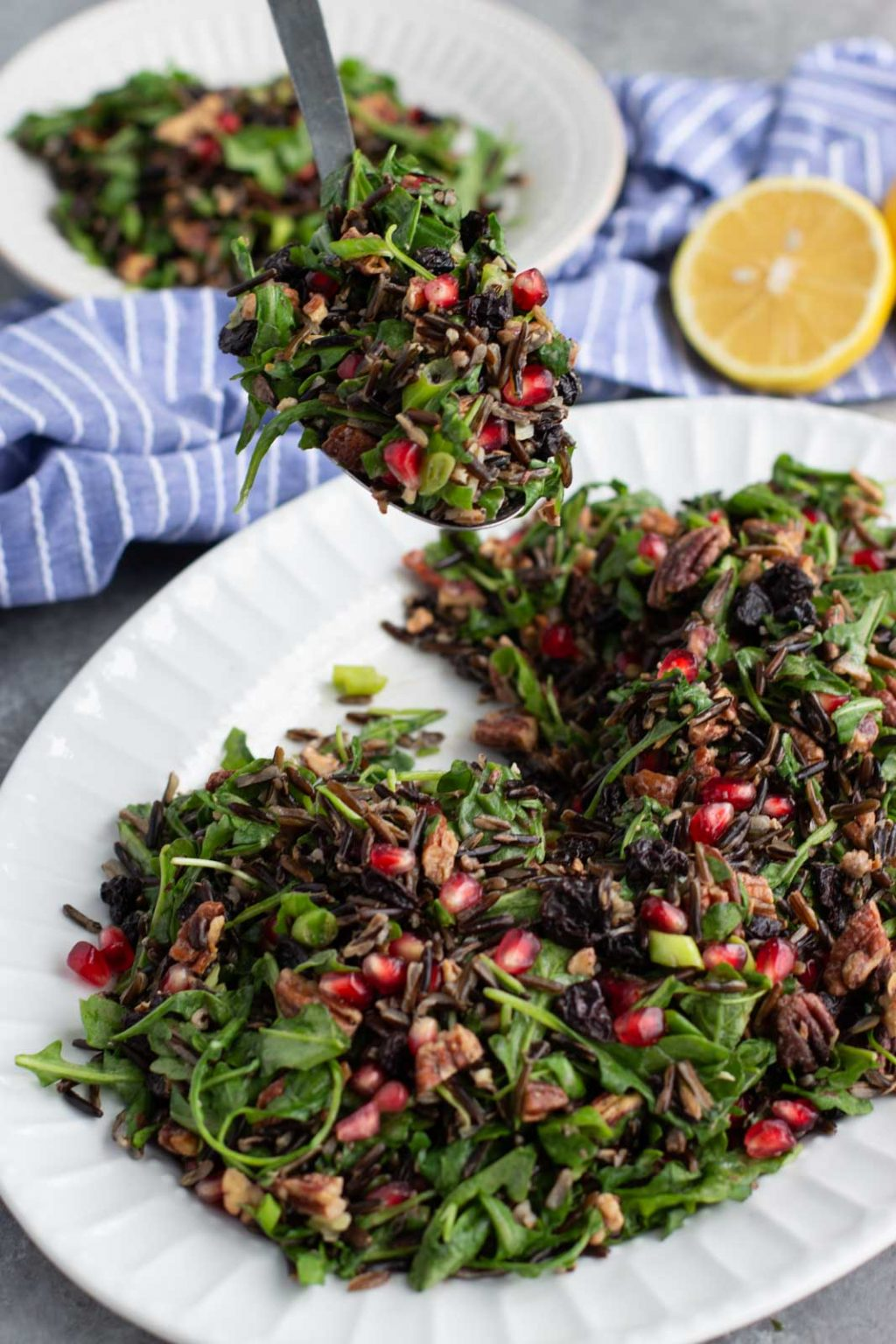A spoon scooping arugula wild rice Christmas salad from a large white platter on a gray background.
