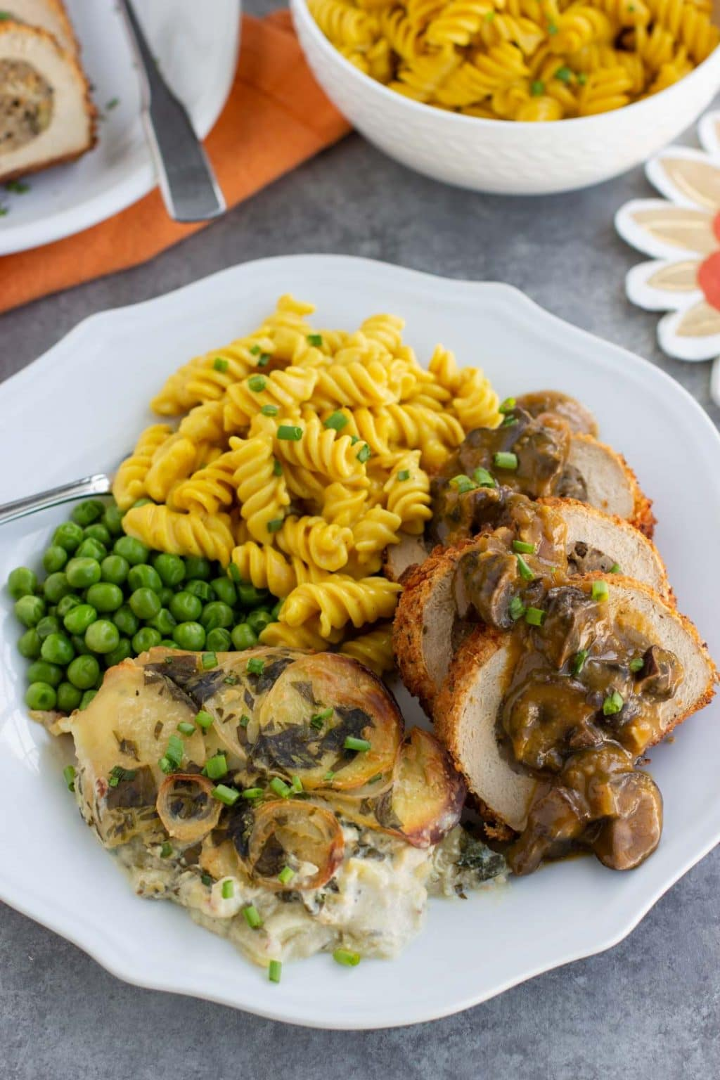 A white plate filled with vegan scalloped potatoes, macaroni and cheese, vegan turkey, and green peas on a gray background.