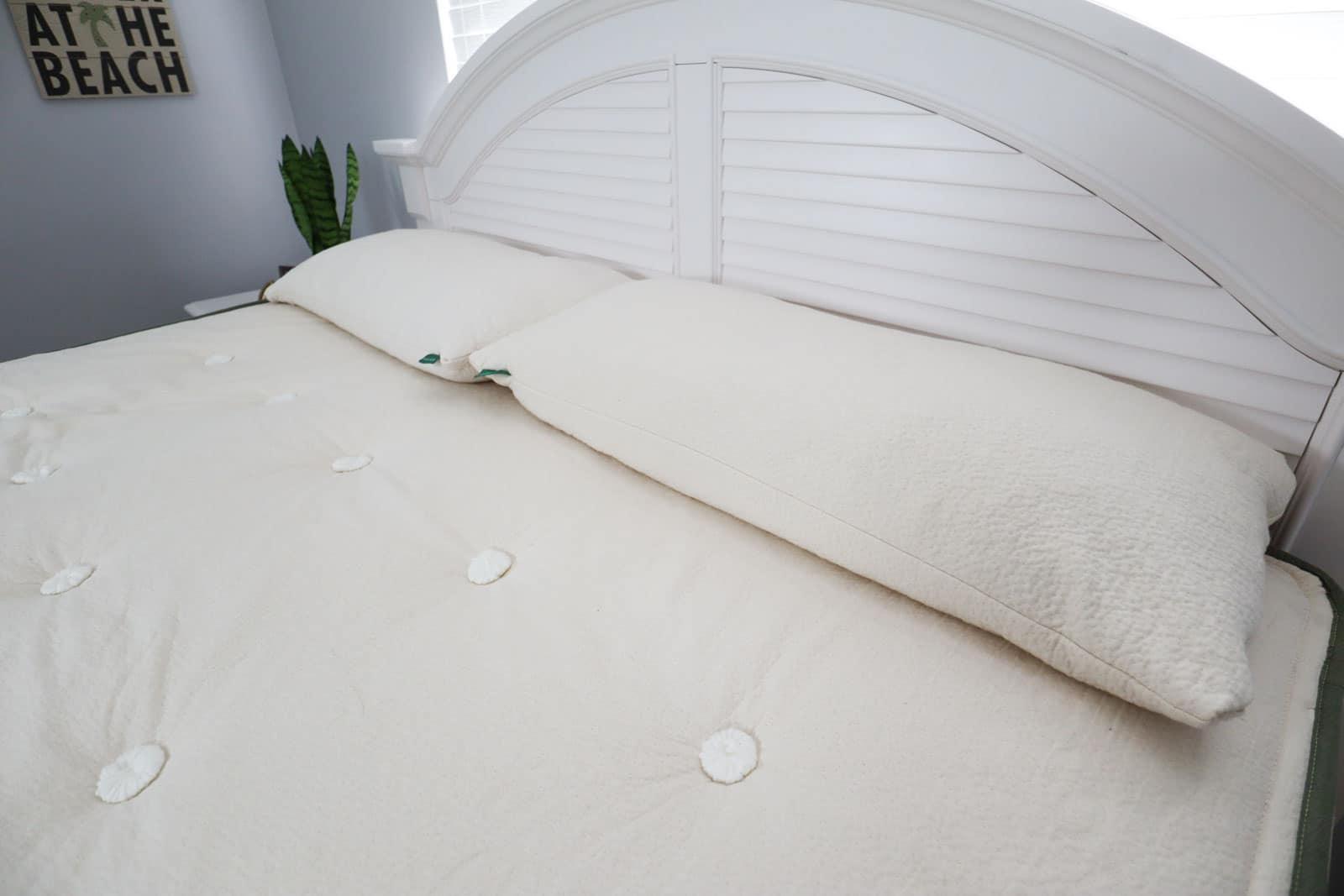A bare mattress with two king pillows sitting top of it next to a white headboard.