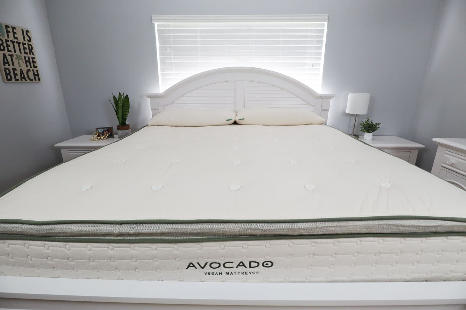 An Avocado Vegan Mattress on a white bed frame in a gray bedroom.