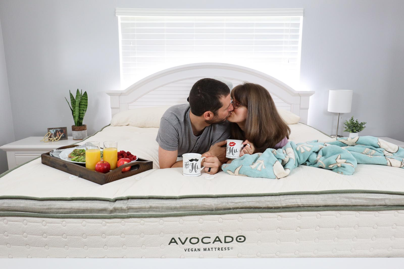 A man and woman kissing on top of an Avocado vegan mattress in a bedroom.