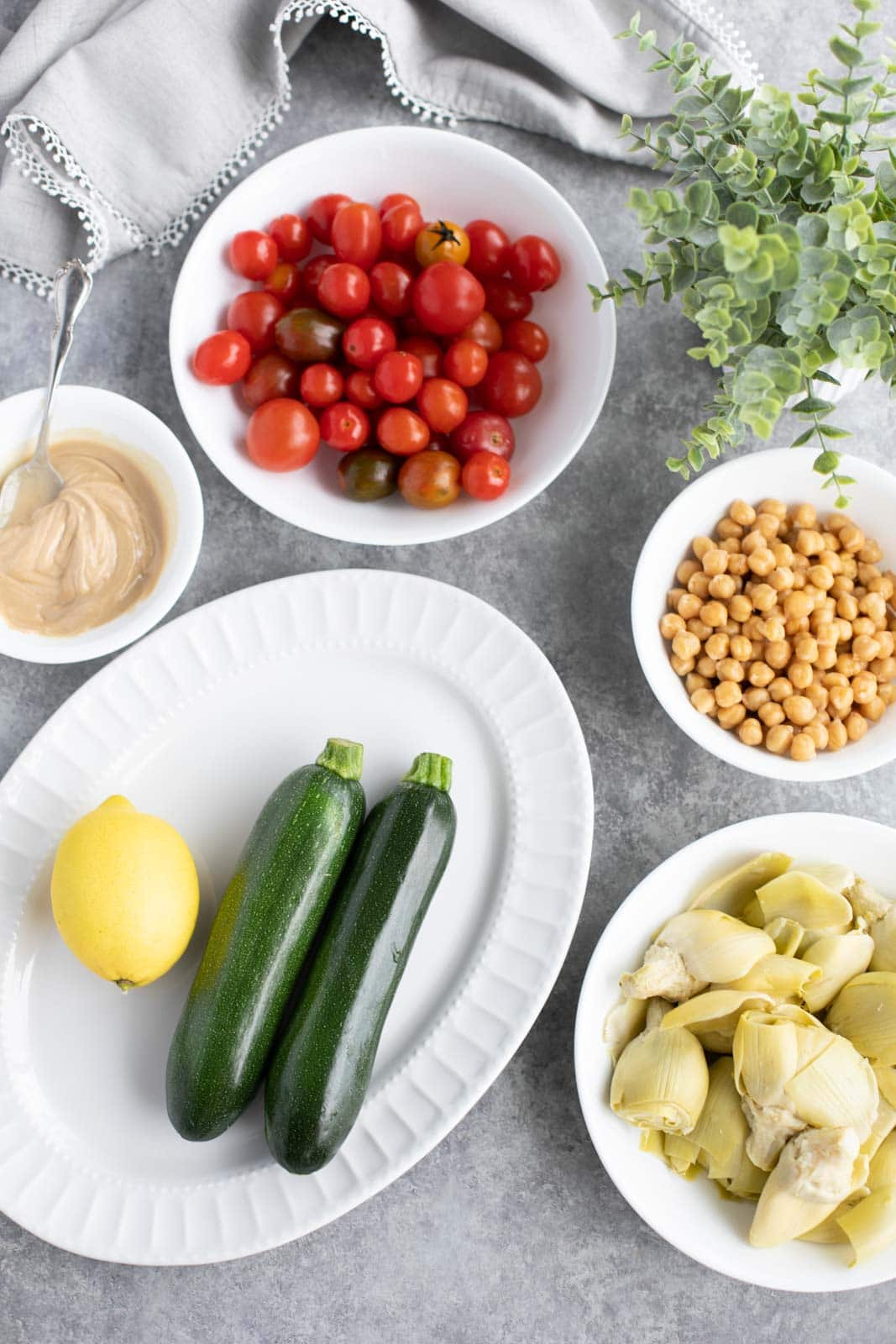 All the ingredients needed to make courgette salad on white plates with a gray background.