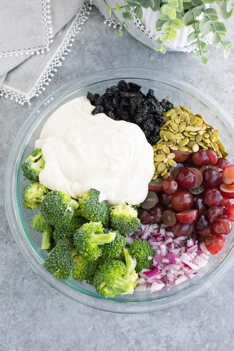 A large clear mixing bowl filled with broccoli, grapes, onions, pumpkin seeds, dried cherries, and creamy dressing on a gray background.