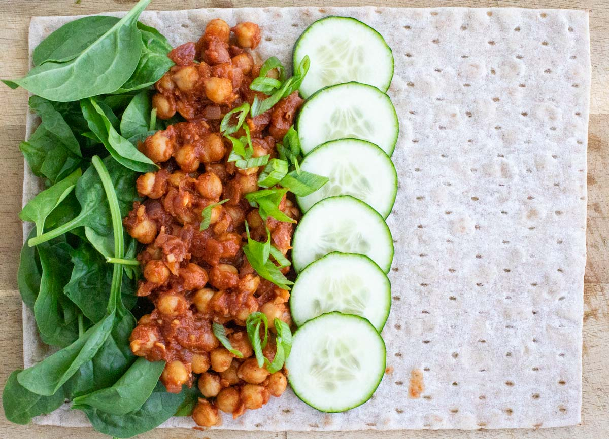A lavash wrap topped with spinach, chickpeas, and cucumbers on top of a wooden cutting board.