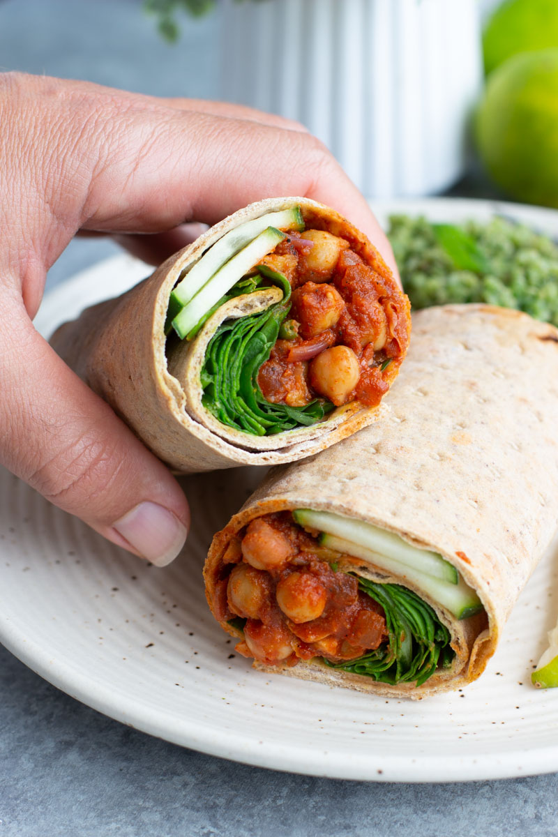 A hand grabbing half of a chickpea lavash wrap that's stacked on top of the other half on a white plate.